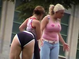 Hot tanned girl was sitting on the grass and three of her friends circled around her to hold th...