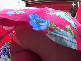 Ebony woman wearing red dress with flowers has her nice ass and panties secretly filmed by upsk...
