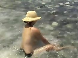 Chinese at beach playing in water with big tits bouncing around