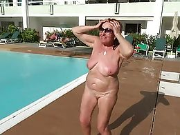 A grown woman is dancing and posing naked in front of the participants of the gay parades and t...