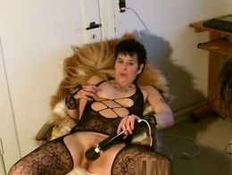 Mature woman with short hair wearing sexy black lingerie uses a vibrator in her small bush puss...