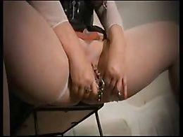 Latex-clad, and hooded, a mega-pierced bitch gets suspended by her breasts