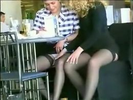 Two ladies in short skirts sit at a restaurant and put on a show, both spreading their legs for...