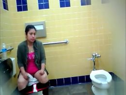 After putting the protective paper down on the toilet bowl the woman drops her pants and sits t...
