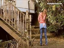 Peeing wetting her jeans pants