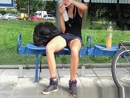 Shaved pussy upskirted on girl wearing shorts resting after riding bike at bus stop.