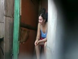 Girl caught by spy camera taking a long pee in an old wood toilet. She cleans her shaved pussy ...