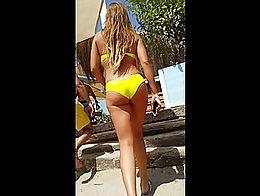 Amazing yellow bikini girl at beach club walking