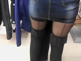 Upskirt on hot woman's shaved pussy in jeans skirt shopping in clothes store.