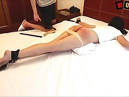 A cute Asian butt gets a taste of belt and paddle during a hard punishment session.