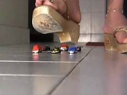 Latina giantess crushes toy cars with wooden sandals