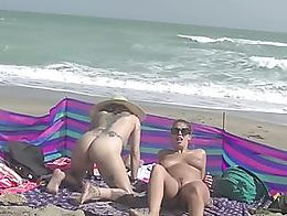 Mrs Brooks and Mrs Ginary take turns eating out each others ass on the nude beach while their h...
