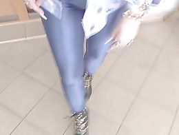 A very busty slutty granny in shiny disco pants and high heels boots smoking a cigarette.