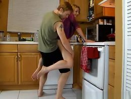 Girl in just purple velvet robe can't reach the top shelves in the kitchen and dude in sho...