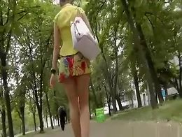 Blonde woman with sexy legs walking in the public garden has her nice ass upskirted by voyeur f...