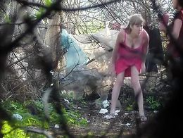 Filming through branches in the woods is a voyeur and two girls go pee as their urination ends ...