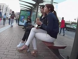 Hot girl in tight pants was sitting on the bench at the bus stop and she had a quick snack whil...