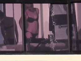 Woman spied, through hotel window, in her bedroom taking off her white robe and dressing her un...
