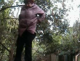 Chubby granny caught pulling down her pants and pissing outdoors next to some bushes.