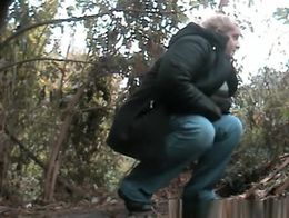 Chubby mature woman caught pulling her pants down and peeing in the nature.