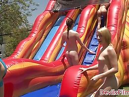 Outdoor lesbians dildo and strapon fucking after playing on jumping castle