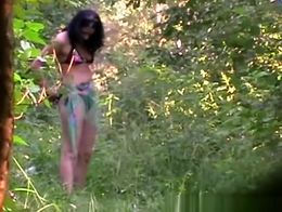 Dark hair woman in bikini goes deep into the woods to take a pee unaware she is secretly being ...