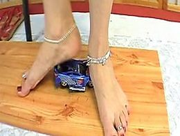 Giantess Rose crushes a toy car with her big feet. Sexy tall european!