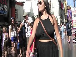 Dark hair woman wearing black short dress gets her ass upskirted in busy street. She as also ni...