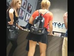 Short hair blonde girl wearing short black skirt upskirted in the clothes store.