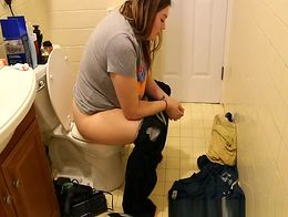 Chubby woman caught seating in bathroom toilet taking a pee and cleaning the pussy.