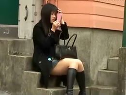 Sexy asian girl was sitting on the stairs and fixing up her makeup with a tiny mirror in her ha...